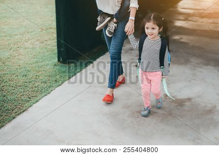 Mother And Pupil Kids Holding Hands Going To School In First Class With Satchel Walking To School Bu