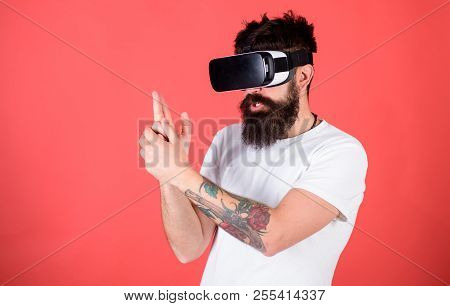 Best shooters for VR. Man bearded hipster with virtual reality headset on red background. First person shooter shows how addictive VR could be. Man hand gesture as gun play shooter game in VR glasses. stock photo