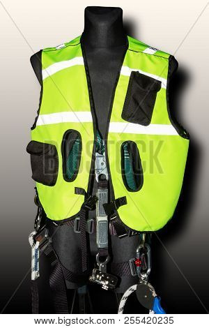 Protective green lightreflect suit for rescue team alpinism mountaineering climbing with metal carbine safety hooks gear for extreme danger situation on black dummy as example of goods in extreme shop stock photo