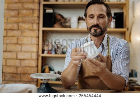 Mature bearded ceramist looking at his handiwork stock photo
