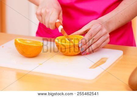 Woman young housewife in kitchen at home slicing fresh orange fruits on cutting board for salad or juicing. Healthy eating, cooking, raw food, dieting and people concept. stock photo