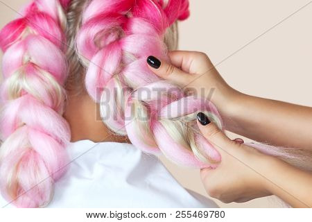 The hairdresser weaves braids with pink kanekalons beautiful blonde beauty salon. stock photo