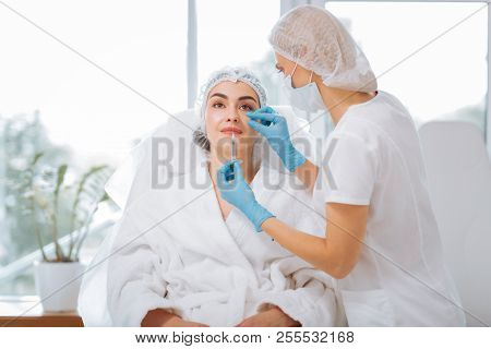 Delighted nice woman having an injection in the lips stock photo