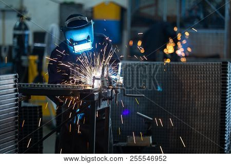 Workers Wearing Industrial Uniforms And Welded Iron Mask At Steel Welding Plants, Industrial Safety
