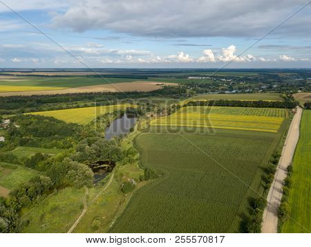 Aerial view from a bird's-eye view to a rural landscape with dirt road, agricultural fields of planted crops in the summer at sunset. View from flying drone. stock photo