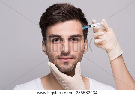 Filler forehead injection for male face in beauty clinic stock photo
