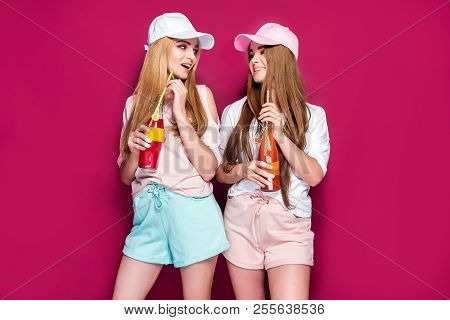 Two lovely young ladies in cute sportswear drinking cold beverages from bottles and looking at camera while standing on magenta background stock photo