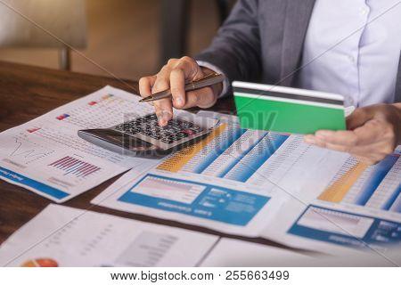 Businesswoman Using Calculator To Calculate Saving Account Passbook ...