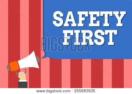 Handwriting text writing Safety First. Concept meaning Avoid any unnecessary risk Live Safely Be Careful Pay attention Man holding megaphone loudspeaker speech bubble message speaking loud. stock photo