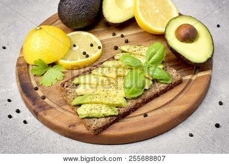 Delicious fresh avocado meal, bread and avocado fruit on a wooden cutting board. Cross section of avocado and lemon, healthy eating or lifestyle theme with concrete background. stock photo