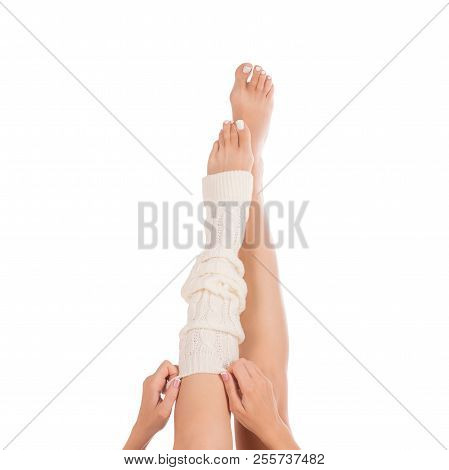 Female legs in white leg warmer. Female hands putting on a gaiter . White pedicure, french manicure. Close up, isolated on white background stock photo