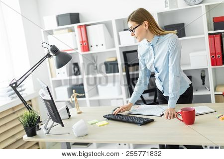A young girl in glasses stands near the table and prints on the keyboard. stock photo