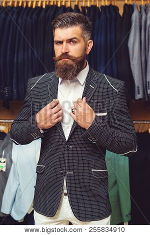sale, shopping, fashion, style and people concept - elegant young brutal bearded man in suit choosing jacket in mall or clothing store. men suit perfect to last detail. Man posing in black suit stock photo