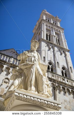 Statue of St Lawrence on St Lawrence square with bell tower of the Cathedral of St. Lawrence and blue sky in the background, Trogir, Croatia,  built in the Romanesque-Gothic style stock photo