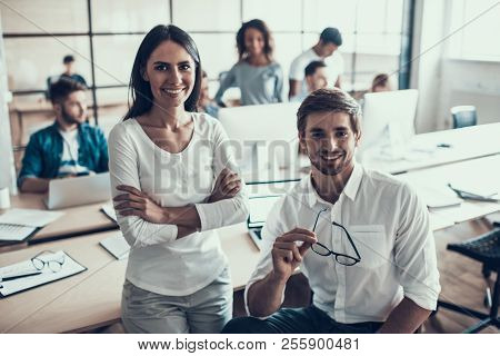 Young Smiling Business People At Work In Office. Portrait Of Young Man And Woman Sitting Next To Gro