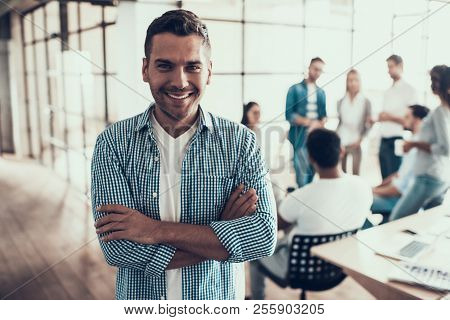 Portrait Of Young Smiling Businessman In Office. Group Of Young Business People On Break In Office.
