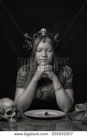 Horned pretty girl preparing to have a dinner stock photo