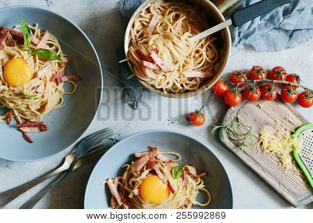 Pasta Carbonara With Bacon And Parmesan In Gray Plates On The Table, Restaurant Serve. Traditional I