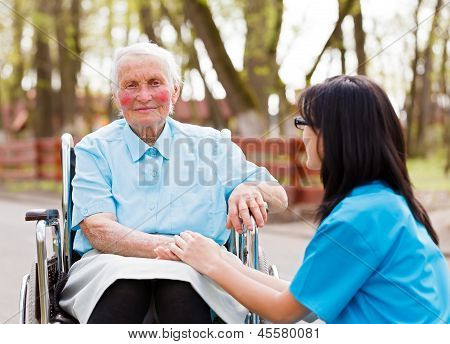 Beautiful doctor nurse in blue coat walking a kind elderly lady in wheelchair in park. stock photo