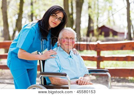 Beautiful doctor nurse in blue coat walking a kind elderly lady in wheelchair in park.