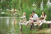 Young glad family with children angling in lake in summer