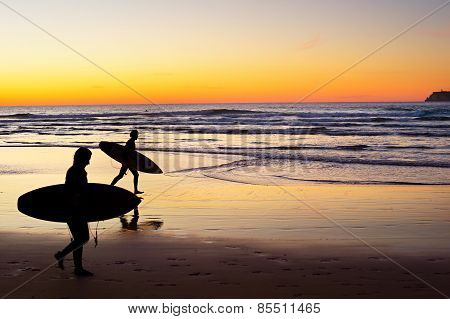 Two surfer running on the beach at sunset. Portugal has one of the best surfing scenes in Europe stock photo