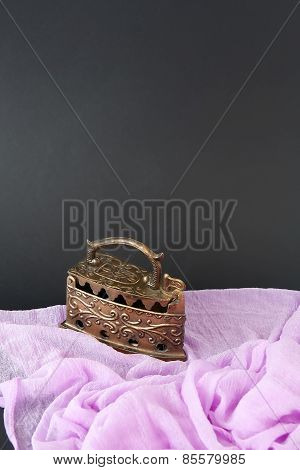 Old iron in action. Pink fabric and black background. stock photo