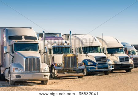 Generic semi truck in perspective row at a parking lot stock photo