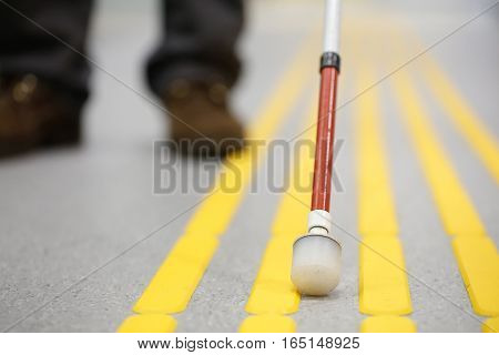 Blind pedestrian walking and detecting markings on tactile paving with textured ground surface indicators for blind and visually impaired. Blindness aid visual impairment independent life concept. stock photo