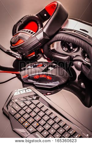 a gaming keyboard mouse headset and Virtual reality glasses shot over a dark reflective surface stock photo