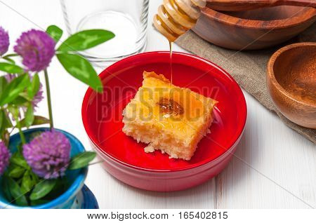 Basbousa - arabian cake with almonds and honey syrup in red bowl on white wooden background stock photo