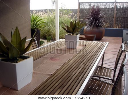 Outdoor table provides pleasant entertaining space and links the house with the garden. stock photo