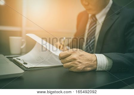 Business man signing a contract . Business man Close-up photo vintage tone Close up of hand of businessman signing a form. Business man signing contract for future deal. Business man signing legal document. Male hand signing employee contract with a bond.