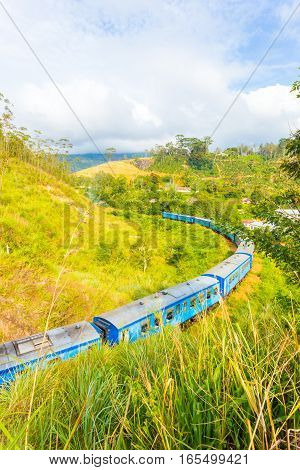 Passenger train moving away on unique circular curving portion of spiral track around a hill in order to gain elevation Demodara Loop at Demodara Railway Station in hill country of Sri Lanka stock photo