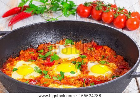 delicious middle east shakshuka - fried eggs onion bell pepper tomatoes chilli and spices in cast iron pan on old wooden background classic recipe close-up stock photo