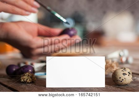 Blank greeting card with hand coloring egg on background. Preparation for Easter, traditional handmade decorations with empty paper. Greeting, art, hobby concept stock photo
