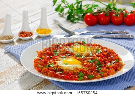 sunny side up eggs with vegetables sprinkled with parsley or shakshuka - bell pepper chili tomato on white dish on table mat. Spices cherry tomatoes on background view from above close-up stock photo