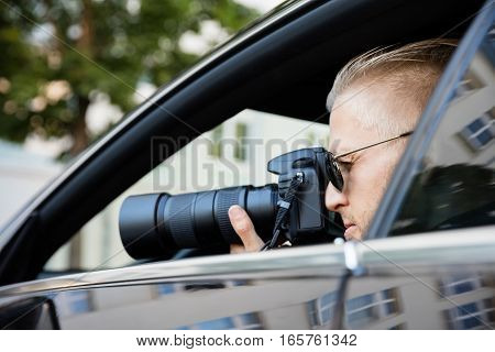Paparazzi Sitting Inside Car Photographing With SLR Camera stock photo
