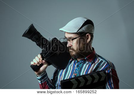 Man Retro movie camera and movie clapper. Bearded thoughtful cinema operator in glasses. The director of documentary and feature films stock photo