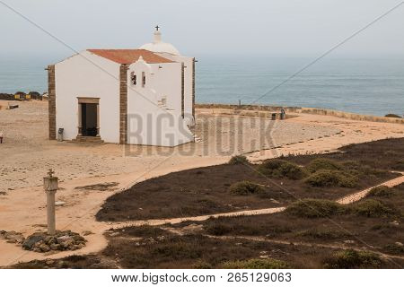 Landscape with a sandy land and Atlantic ocean.  White church with bells and a cross. Cloudy sky. Fortress in Sagres, Portugal. stock photo