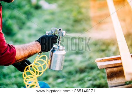 Industrial man painting brown timber using spray gun and air compressor stock photo