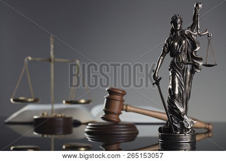 Law and justice concept background. Themis, mallet, scale and legal book on the gray background. stock photo