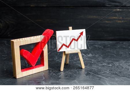 Stand with a red up arrow and a check mark. The concept of high voter turnout, the growth of statistical indicators. Voting, high rating. Raising the popularity of politicians parties selective focus stock photo