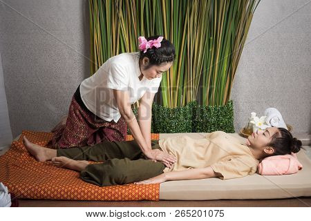 Thai Masseuse doing massage for lifestyle woman in spa salon. Asian beautiful woman getting Thai herbal massage compress massage in spa.She is very relaxed. Healthy Concept. stock photo