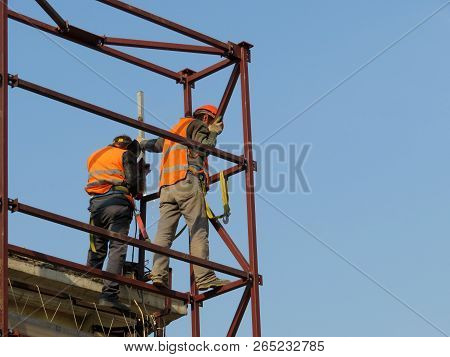 Welders working on the construction site against the clear blue sky. Construction workers on scaffolding, welding work stock photo