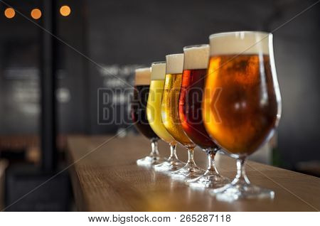 Glasses with different sorts of craft beer on wooden bar. Tap beer in pint glasses arranged in a row