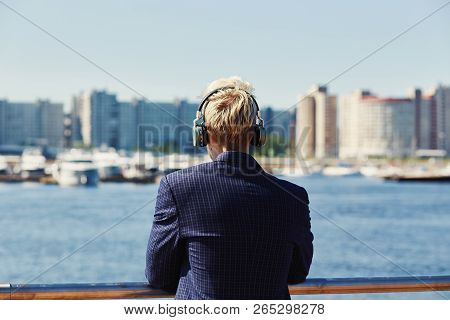Blond male in glasses standing at water holding hands on metal railing and looking away on bright summer day with suspension bridge on background stock photo