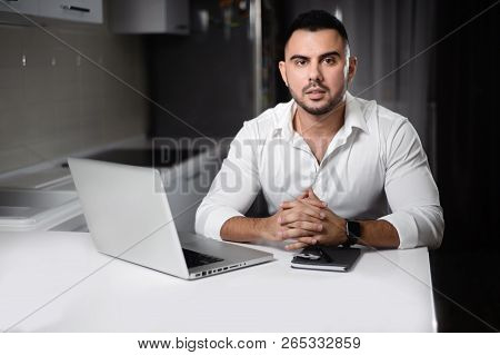 man in white shirt websurfing with laptop in home kitchen stock photo