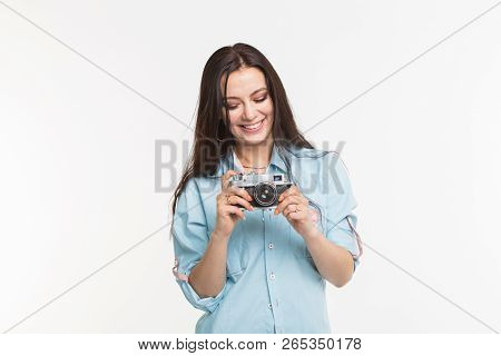 Happy european female model with dark hair enjoying indoor photoshoot. Young woman is looking at her vintage camera on white background stock photo