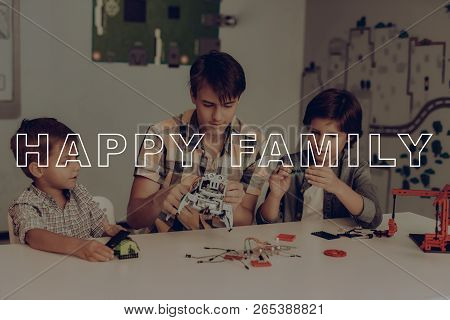 Two Little Boys And Young Guy Robots Constructing. Plaid Flannel. Older Brother. Home Leisure. Children Holiday Activity. Weekend With Friend. Family Relationship. Constructor Toy. Smart Kids. stock photo